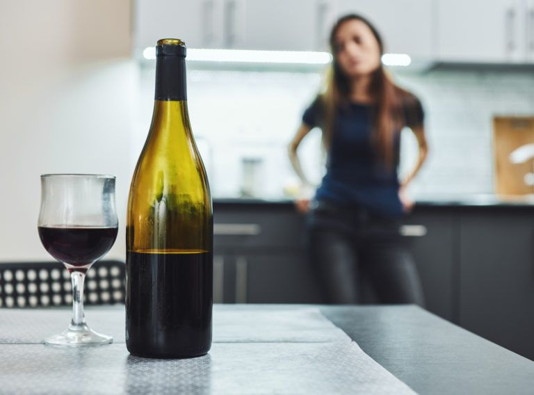 Bottle and glass of red wine standing on the table in kitchen. Woman in the background, looking at it. Female alcoholism concept. Protest in the treatment of alcohol addiction. Toper, drunkard, drunk, drinker. Blurred background